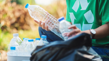 Person picking up plastic bottles for recycling image